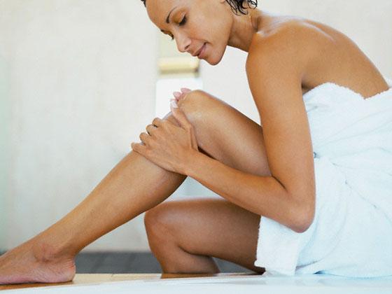 Woman touching her leg --- Image by © Whisson/Jordan/Corbis