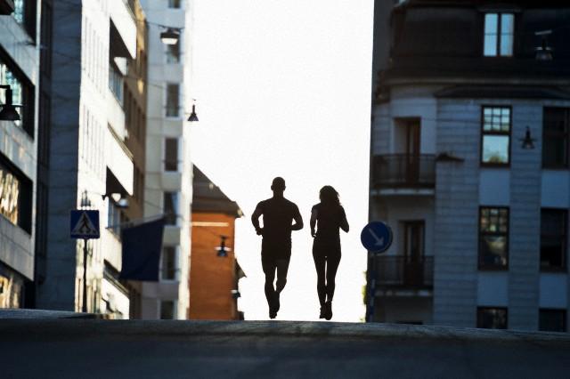 Couple running on road, Stockholm, Sweden