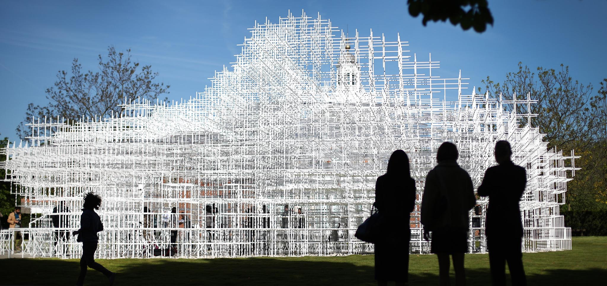 LONDON, ENGLAND - JUNE 04:  Visitors look at the Serpentine Gallery Pavilion on June 4, 2013 in London, England. Designed by Japanese architect Sou Fujimoto, it occupies 357 square-metres of the lawn in front of the gallery. Using a latticed structure of 20 mm steel poles with a cafe sited inside, visitors are encouraged to enter and interact with the Pavilion in different ways throughout it's month tenure in London's Kensington Gardens.  (Photo by Peter Macdiarmid/Getty Images)