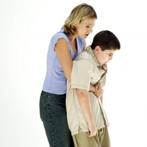 Woman Performing the Heimlich Maneuver on a Boy (10-12) --- Image by © Royalty-Free/Corbis